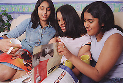 Group of teenage girls sitting on sofa; drinking tea and reading magazine,