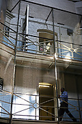 A prisoner walking past the E wing in the central star. The central star leads to all wings of Wandsworth prison. HM Prison Wandsworth is a Category B men's prison at Wandsworth in the London Borough of Wandsworth, South West London, United Kingdom. It is operated by Her Majesty's Prison Service and is one of the largest prisons in the UK with a population over 1500 people. (photo by Andy Aitchison)