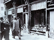 Pedestrians glance at the broken windows of a Jewish owned shop in Berlin after the attacks of Kristallnacht, November 1938