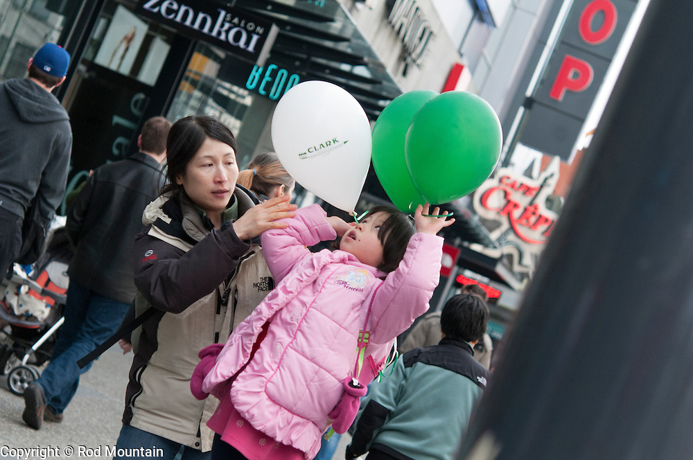 A young girl positions her balloons on St. Patrick's Day in Vancouver, British Columbia.