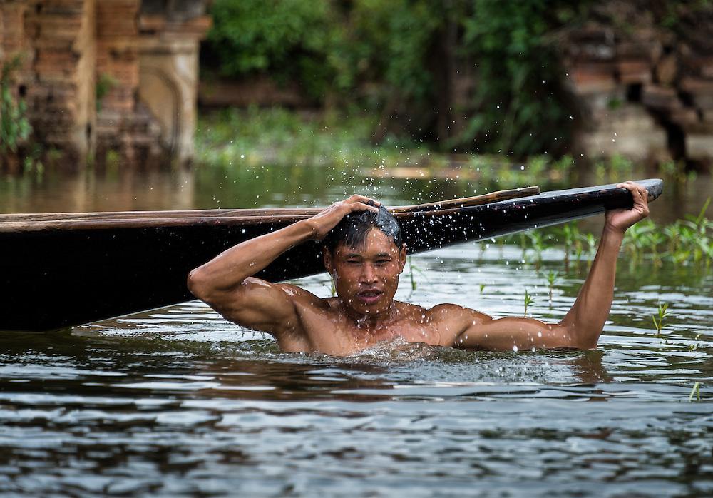 INLE LAKE, MYANMAR - CIRCA DECEMBER 2013: Burmese man taking a bath in Sankar village (or Samka ). A small village located in the south of Inle Lake.