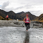 Runner Gaelle Macdonald crosses  Moke Creek on the Ben Lomond High Country Station during the Pure South Shotover Moonlight Mountain Marathon and trail runs. Moke Lake, Queenstown, New Zealand. 4th February 2012. Photo Tim Clayton