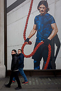 Stylish and athletic model on a billboard for clothing retailer H&M, in central London. We see a male model holding a red rope, seemingly about to loop it over two men walking beneath the ad. In 1947 Hennes women's clothing store opened in Västerås, Sweden. Today the H&M Group offers fashion for everyone under the brands of H&M, COS, Monki, Weekday, Cheap Monday and & Other Stories, as well as fashion for the home at H&M Home.