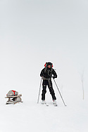 Skiing in the falling snow by a typical DNT waymarker cairn of rocks with a red painted T. Returning from an overnight trip to the Danskehutte.