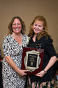 Tina Broyles, left, presents Kim Parker of Kim Parker Plantscapes Inc., with the Business Person of the Year award during the Milpitas Chamber of Commerce 59th Annual Awards and Installation Banquet at Sheraton San Jose Hotel in Milpitas, California, on July 28, 2016. (Stan Olszewski/SOSKIphoto)