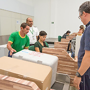 CAPTION: Anaesthesiologist Dr Melo ensures that the team's supplies are checked in properly. The boxes hold medicines, medical equipment and other items needed for the operations that the team will shortly be conducting, deep inside the Amazon. They usually carry everything they might need, as the remote hospitals they visit may lack all that's needed for safe and effective surgeries. LOCATION: Eduardo Gomes International Airport, Manaus, Amazonas, Brazil. INDIVIDUAL(S) PHOTOGRAPHED: Dr Theomário Melo (right).