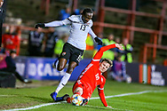 Wales midfielder Lee Evans slides in and tackles Trinidad and Tobago midfielder Nathan Lewis during the Friendly European Championship warm up match between Wales and Trinidad and Tobago at the Racecourse Ground, Wrexham, United Kingdom on 20 March 2019.