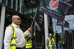 London, UK. 5th August, 2021. Alberto Durango, General Secretary of the Cleaners and Allied Independent Workers Union (CAIWU), holds a flag during a protest by night-shift cleaners outside the UK headquarters of Facebook. The cleaners are outsourced via the Churchill Group to clean the Facebook offices and CAIWU claims that five additional floors have been added to their workload, that cleaners who have left have not been replaced and that sickness and holiday cover has not been provided.