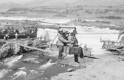 9305-B7340. 3 Indians in a Seufert cable car returning from Standing island. They are being towed to the Oregon shore by a gasoline engine at the upper cable terminus. ca. 1940