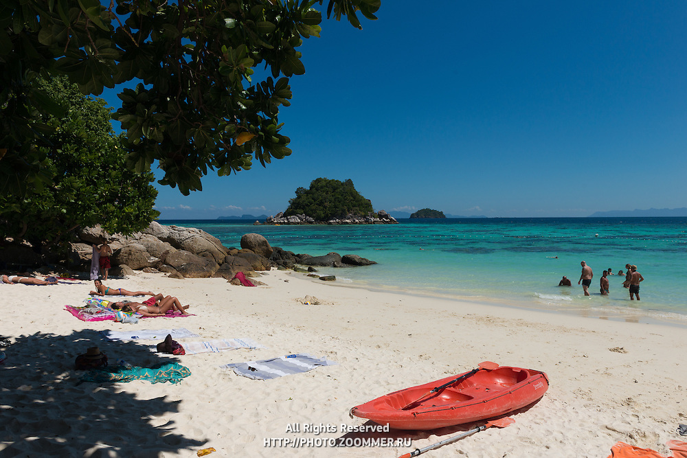 People sunbathing on small private beach of Serendipity hotel, Ko Lipe, Thailand