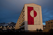 """Greenland flag mural on apartment block P, Nuuk, Greenland. Block P is the largest apartment blog in downtown Nuuk, the capital of Greenland.  More than 1% of Greenland's 57,000 population reportedly live in this building. On the end is the Greenland flag. This image was made just two days before the June 21st 2009 self-governance ceremony, in which Denmark handed over more power to the local population. Block P was built by the Danish government in the 1960s to modernize and urbanize the Greenlandic infrastructure by moving people away from coastal settlements which were though to be """"unprofitable, unhealthy and unmodern"""". The same could be said for these 'new' buildings. Block P was demolished in October 2012. Copyright 2009 Dave Walsh"""