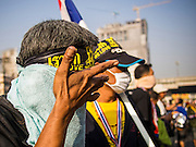 26 DECEMBER 2013 - BANGKOK, THAILAND: A Thai protestors wipes tear gas out of his eyes on Rama IX Road near the Thai Japan Stadium complex. Thousands of anti-government protestors flooded into the area around the Thai Japan Stadium to try to prevent the drawing of ballot list numbers by the Election Commission, which determines the order in which candidates appear on the ballot of the Feb. 2 election. They were unable to break into the stadium and ballot list draw went as scheduled. The protestors then started throwing rocks and small explosives at police who responded with tear gas and rubber bullets. At least 20 people were hospitalized in the melee and one policeman was reportedly shot by anti-government protestors.      PHOTO BY JACK KURTZ