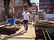 05 MARCH 2017 - KATHMANDU, NEPAL: A Nepali man walks through an empty lot being rebuilt after the 2015 earthquake. Much of Kathmandu is now a construction site because of rebuilding  two years after the earthquake of 25 April 2015 that devastated Nepal. In some villages in the Kathmandu valley workers are working by hand to remove ruble and dig out destroyed buildings. About 9,000 people were killed and another 22,000 injured by the earthquake. The epicenter of the earthquake was east of the Gorka district.     PHOTO BY JACK KURTZ