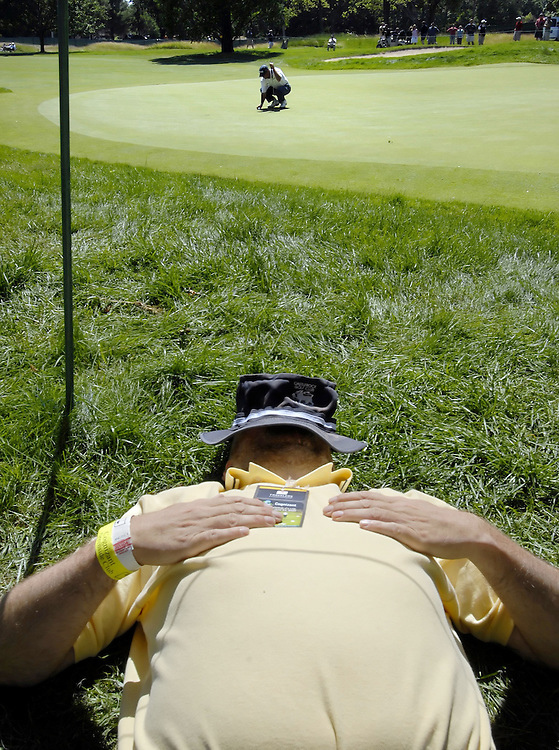 Chris DiMarco, top, lines up his putt on the seventh hole as a parton rests in the sun during the third round of the Travelers Championship golf tournament in Cromwell, Conn.