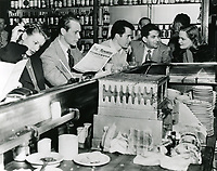 1945 Actor, Jess Barker (reading the Hollywood Reporter), Larry Parks and Sidney Skolsky speaking with lady at Schwab's Pharmacy