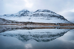 A snow-covered mountain is reflected in the water on the west coast of Iceland.
