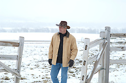 cowboy walking on a ranch in the snow