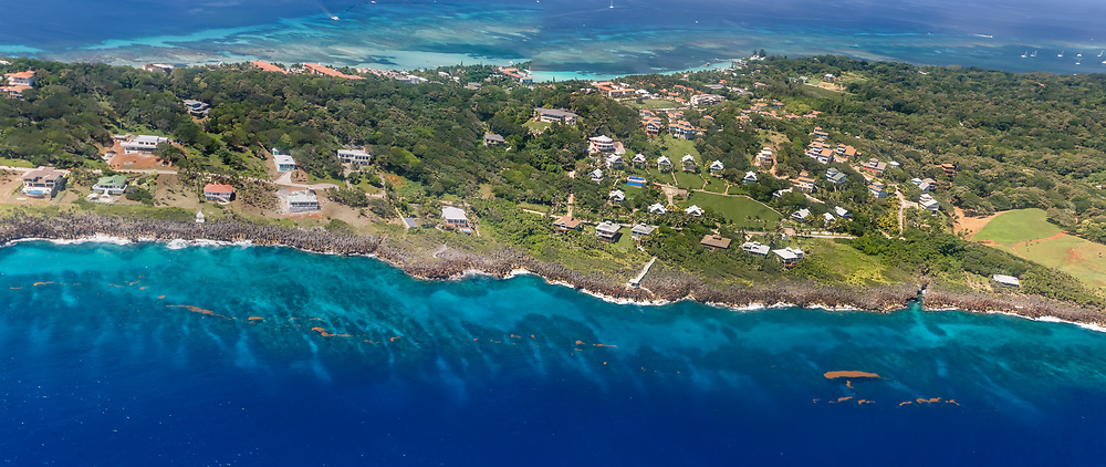 Aerial panoramic of the deep blues and green colors of Roatan Island and surrounding coral reefs