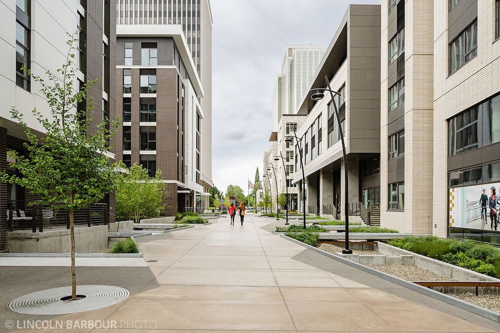 Two women walk through a pathway between buildings.  Everything looks new and clean with modern design elements.