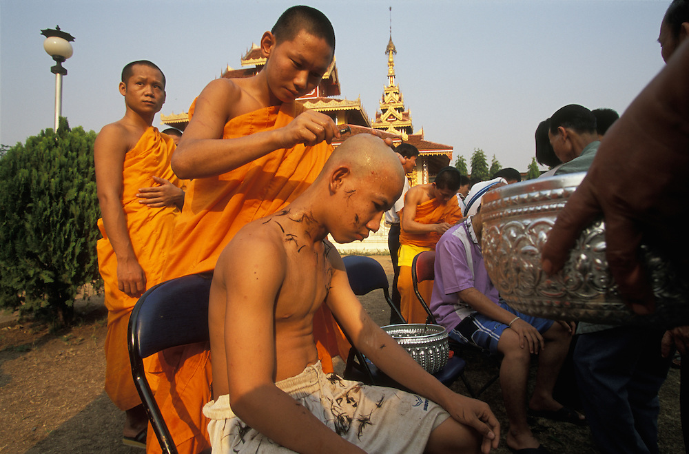 A Shan boy gets his head shaved during Poy Sang Long, a yearly ceremony at which boys are ordained as novice monks, Mae Hong Son, Thailand. The shaving takes place inside the Buddhist temple Wat Hua Wiang. Practically every Shan boy goes through this three-day ceremony sometime between the age of eight and fourteen. After the ordination, the boy spends about one month in a Buddhist monastery and then usually returns to normal life again.