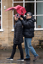 © Licensed to London News Pictures. 08/02/2019. Bourton-on-the-Water, Gloucestershire, UK. Tourists struggle with their umbrellas as they cross a bridge during a rain shower on a wet and windy day in Bourton-on-the-Water in Gloucestershire, UK. Photo credit: LNP