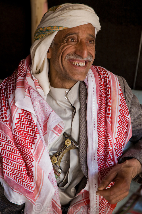 Ahmed Ahmed Swaid, a qat merchant, sits on a rooftop in the old Yemeni city of Sanaa. (Ahmed Ahmed Swaid is featured in the book What I Eat: Around the World in 80 Diets.) The caloric value of his typical day's worth of food in the month of April was 3300 kcals. He is 50 years of age; 5 feet, 7 inches tall; and 148 pounds. Ahmed, who wears a jambiya dagger as many Yemeni men do, has been a qat dealer in the old city souk for eight years. Although qat chewing isn't as severe a health hazard as smoking tobacco, it has drastic social, economic, and environmental consequences. When chewed, the leaves release a mild stimulant related to amphetamines. Qat is chewed several times a week by a large percentage of the population: 90 percent of Yemen's men and 25 percent of its women. Because growing qat is 10 to 20 times more profitable than other crops, scarce groundwater is being depleted to irrigate it, to the detriment of food crops and agricultural exports. MODEL RELEASED.