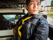 17 JUNE 2015 - RANGAE, NARATHIWAT, THAILAND:  A Thai Army woman Ranger looks out the back of an unarmored pickup truck during a mission in an area where there's been a lot of insurgent activity. There are 5 platoons of women Rangers serving in Thailand's restive Deep South. They generally perform security missions at large public events and do public outreach missions, like home wellness checks and delivering food and medicine into rural communities. The medics frequently work in civilian clothes because the Rangers found people are more relaxed around them when they're in civilian clothes. About 6,000 people have been killed in sectarian violence in Thailand's three southern provinces of Narathiwat, Pattani and Yala since a Muslim insurgency started in 2004. Attacks usually spike during religious holidays. Insurgents are fighting for more autonomy from the central government in Bangkok.    PHOTO BY JACK KURTZ