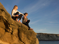 Girls sitting on rock at beach in Northern Spain