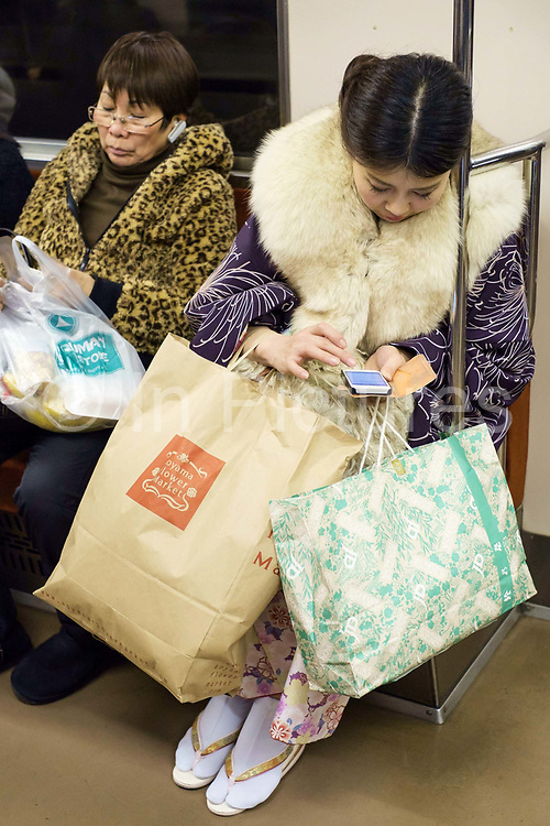 Young women on their smart phones with their shopping on the subway. Tokyo, Japan