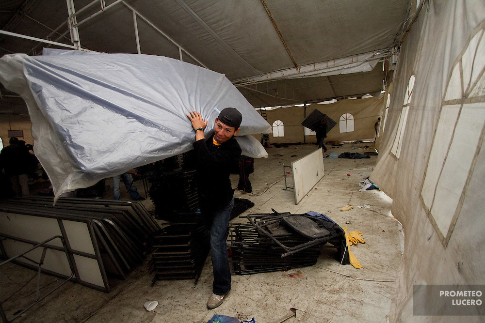 """A volunteer carries a mat used in the temportary migrants shelter in Tultitlán on  August 3rd, 2012. Tultitlán local authorithies ordered to dismantle the temporary shelter that was placed under a bridge in Tultitlán after shelter  """"San Juan Diego Cuauhtlatoatzin"""" in Lecheria, was closed on July 9th, 2012. (Photo: Prometeo Lucero)"""