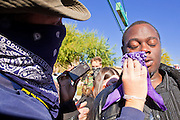 30 NOVEMBER 2011 - PHOENIX, AZ:   Street medics help a man pepper sprayed by Phoenix police at an anti-ALEC protest in Phoenix Wednesday. Police pepper sprayed the crowd several times and arrested six or seven people during the melee. About 300 people picketed the American Legislative Exchange Council (ALEC) conference at the Westin Kierland Resort and Spa in Phoenix, AZ, Wednesday. The protesters claim ALEC, a conservative think tank, violates its tax exempt status by engaging in lobbying, a charge ALEC officials deny. Many conservative pieces of legislation, like Arizona's anti-immigration bill SB1070, originate with ALEC conferences (SB 1070 originated at an ALEC conference several years ago). Many of the protesters are also members of the Occupy movement.     PHOTO BY JACK KURTZ