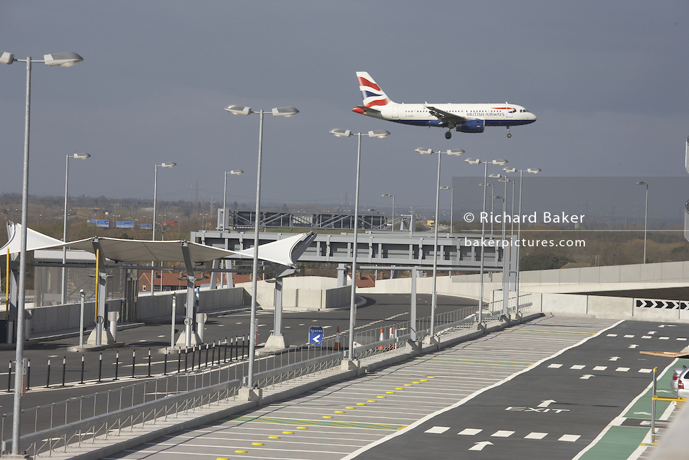 British Airways Airbus lands over unused car parking bays outside newly-opened London Heathrow Airport's Terminal 5 building.