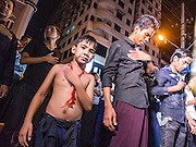 04 NOVEMBER 2014 - YANGON, MYANMAR: Burmese Shia Muslims walk through Yangon pounding their chests during an Ashura procession Monday night. Ashura commemorates the death of Hussein ibn Ali, the grandson of the Prophet Muhammed, in the 7th century. Hussein ibn Ali is considered by Shia Muslims to be the third imam and the rightful successor of Muhammed. He was killed at the Battle of Karbala in 610 CE on the 10th day of Muharram, the first month of the Islamic calendar. According to Myanmar government statistics, only about 4% of the population is Muslim. Many Muslims have fled Myanmar in recent years because of violence directed against Burmese Muslims by Buddhist nationalists.    PHOTO BY JACK KURTZ