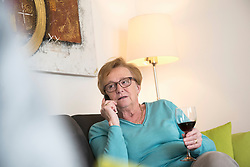 Old woman relaxing on sofa with a glass of red wine and talking on phone