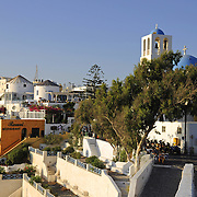 Thira the capital town of Santorini island with blue domed chapel and bell tower at sunset