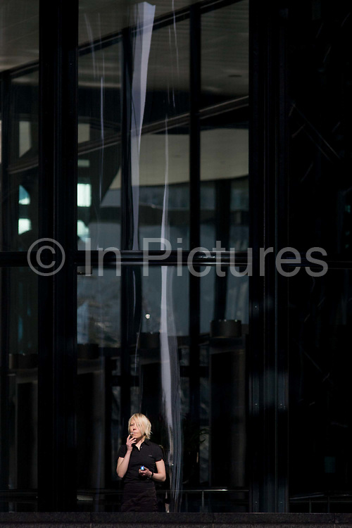 An office employee takes a cigarette break outside corporate offices in the City of London. Looking guilty and aware, she inhales on her tobacco while holding the packet in her left hand. Above her head is the steel architecture with the backdrop of the Broadgate development within the ancient boundary of the capital's Square Mile, it's financial district founded by the Romans in AD43.