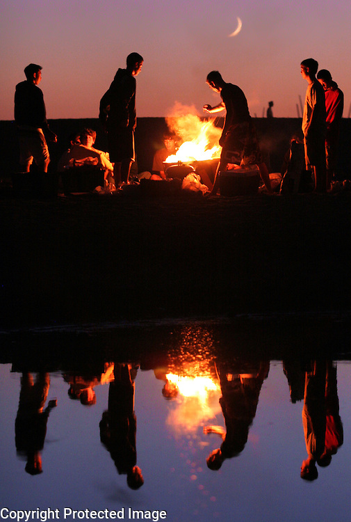 A crescent moon rises over a Twin Lakes State Beach in Santa Cruz, California as a bonfire is reflected in the outflow from Schwans Lagoon.<br /> Photo by Shmuel Thaler <br /> shmuel_thaler@yahoo.com www.shmuelthaler.com