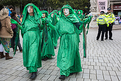 London, UK. 9 October, 2019. Climate activists from the Extinction Rebellion Green Brigade pass through Trafalgar Square on the third day of International Rebellion protests to demand a government declaration of a climate and ecological emergency, a commitment to halting biodiversity loss and net zero carbon emissions by 2025 and for the government to create and be led by the decisions of a Citizens' Assembly on climate and ecological justice.