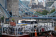 As a tourist boat passes beneath Tower Bridge, locked-up bikes are on a boat at Tower Bridge Moorings are grouped together on the river Thames, on 11th June 2021, in London, England. Tower Bridge Moorings is the capital's only floating gardens - a sustainable way of living for a community of more than one hundred adults and children, and a shelter for wildlife on the river. Tower Bridge Moorings is the capital's only floating gardens - a sustainable way of living for a community of more than one hundred adults and children, and a shelter for wildlife on the river.