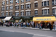 Young people form a long queue outside Bunsik on 3rd July 2021 in London, United Kingdom. Bunsik is a generic term used to refer to inexpensive Korean dishes available at bunsikjeom or bunsikjip snack restaurants. Since the term bunsik literally means food made from flour, foods such as ramyeon and bread can be considered bunsik.