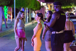 © Licensed to London News Pictures.  02/07/2021. Magaluf, Spain. A bouncer makes a hair bun while holidaymakers from England make the most of a Friday night in Magaluf as Balearic Islands were added on the UK 'green list' on Wednesday. Photo credit: Marcin Nowak/LNP
