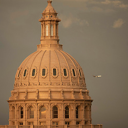 An airplane heads to Austin-Bergstrom airport following a rainstorm over the Texas Capitol dome in Austin while a spring weather system blows through central Texas. The mammatocumulus are characterized by cotton-like puffiness and dramatic formations.