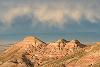 Evaporating rain known as virga hangs in the air above the McCullough Peak Badlands. In the background the Pryor Mountains can be seen.