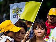 29 NOVEMBER 2017 - YANGON, MYANMAR:  People walk through the grounds of the Papal Mass with a Vatican flag. Hundreds of thousands of Catholics from Myanmar attended the mass said by Pope Francis at Kyaikkasan Sports Ground in Yangon Wednesday. Pope Francis is on the first visit by a Pope to Myanmar.   PHOTO BY JACK KURTZ