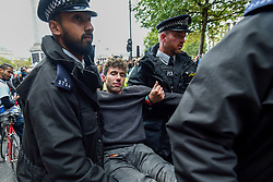 © Licensed to London News Pictures. 10/10/2019. LONDON, UK. An activist is removed by police after being extracted from atop a wooden structure, in Trafalgar Square during day 4 of Extinction Rebellion's climate change protest in the capital.  Activists are calling on the Government to take immediate action against the negative impact of climate change.  Photo credit: Stephen Chung/LNP