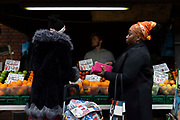 Two women, one unzipping her purse, purchase fresh produce at an outdoor fruit and vegetable market stall on 4th September, 2021 in Leeds, United Kingdom. A combination of Brexit and Covid-19 is reportedly exacerbating an already severe staff shortage in the British food industry, with a lack of fruit and vegetable pickers that could see a hike in food prices across the country.