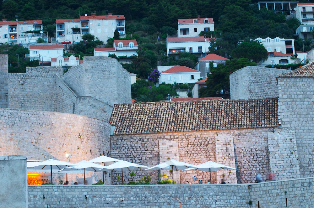 The city wall and fortress, a cafe restaurant with sun shade umbrellas. in evening blue light Dubrovnik, old city. Dalmatian Coast, Croatia, Europe.