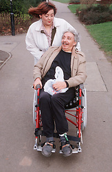 Carer pushing man with disability in manual wheelchair along pavement,