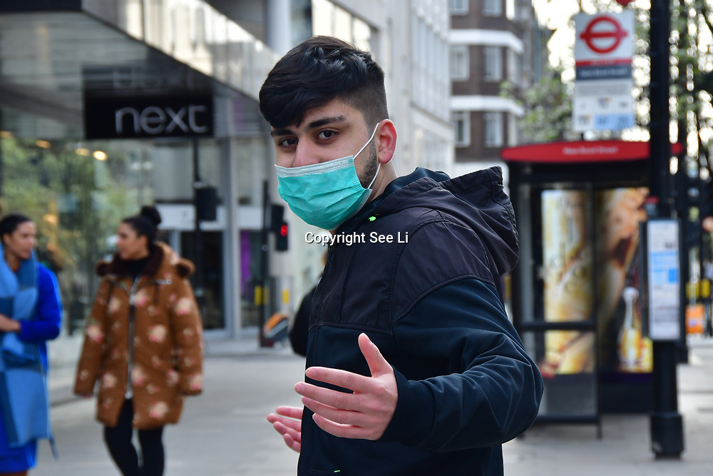 A Asian guy wearing a mask at street during Coronavirus - Pandemic hit Oxford Street many shops closure a few open but empty on 21 March 2020, UK.