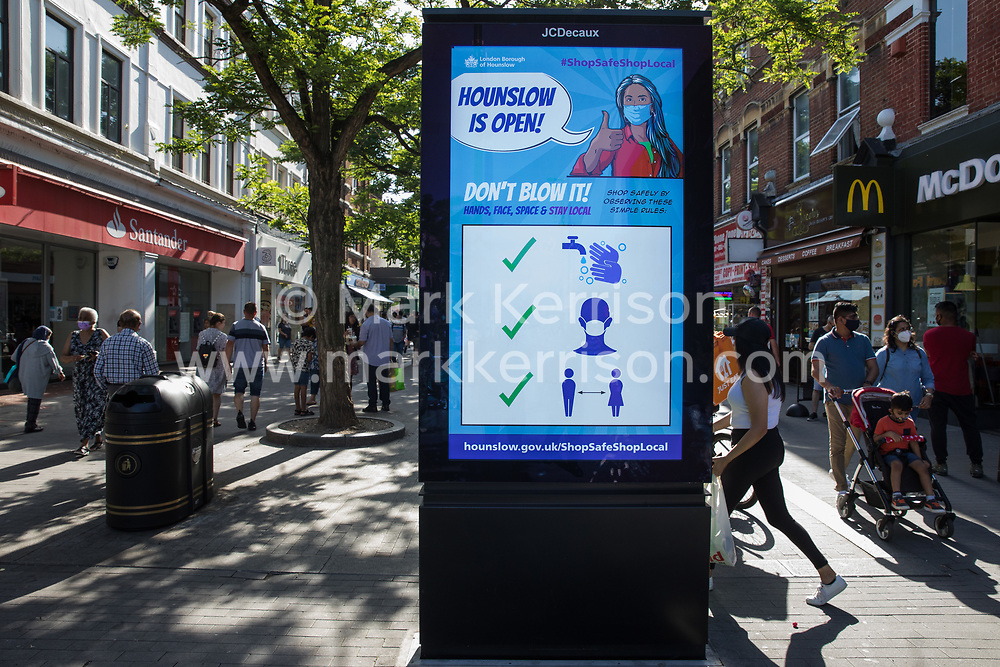 Members of the public pass a London Borough of Hounslow Covid-19 public information display urging residents to take precautions to minimise the spread of the coronavirus amid rising concern regarding the Delta variant on 17th July 2021 in Hounslow, United Kingdom. The UK government is currently still expected to lift almost all restrictions on social contact on 19th July, known as 'Freedom Day', but the current wave driven by the Delta variant is not expected to peak until mid-August.
